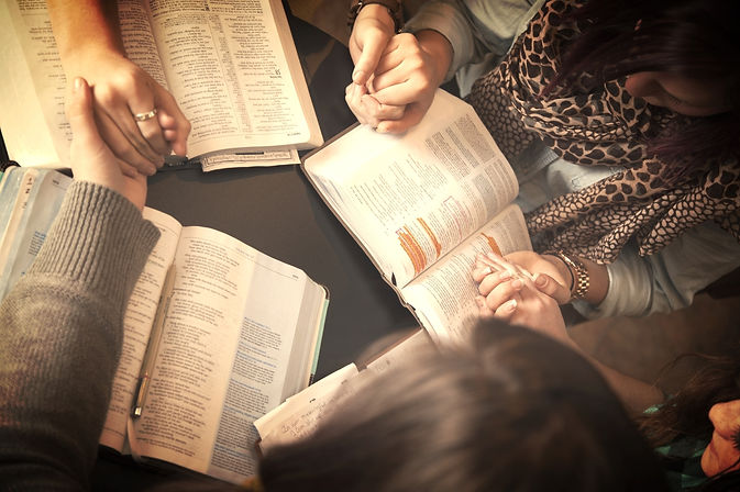 women+bow+and+pray+over+bibles.jpg