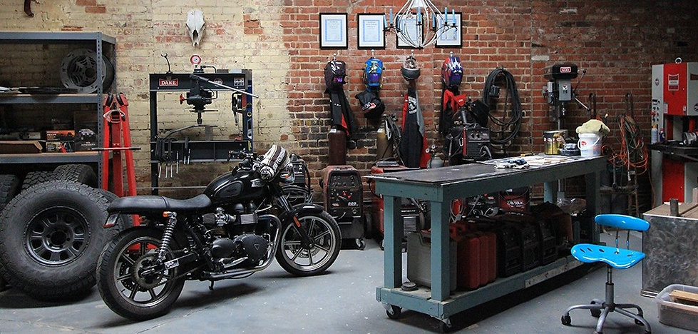 workshop with distressed brick wall, welding helmets, welding jackets, Triumph Bonneville, welding table, in a womens workspace