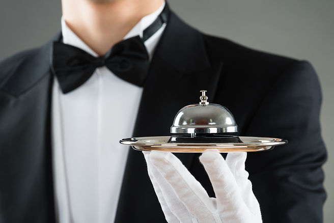 Midsection of waiter holding service bel