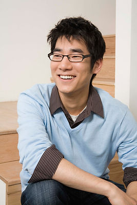 Smiling man with glasses and a blue shirt.