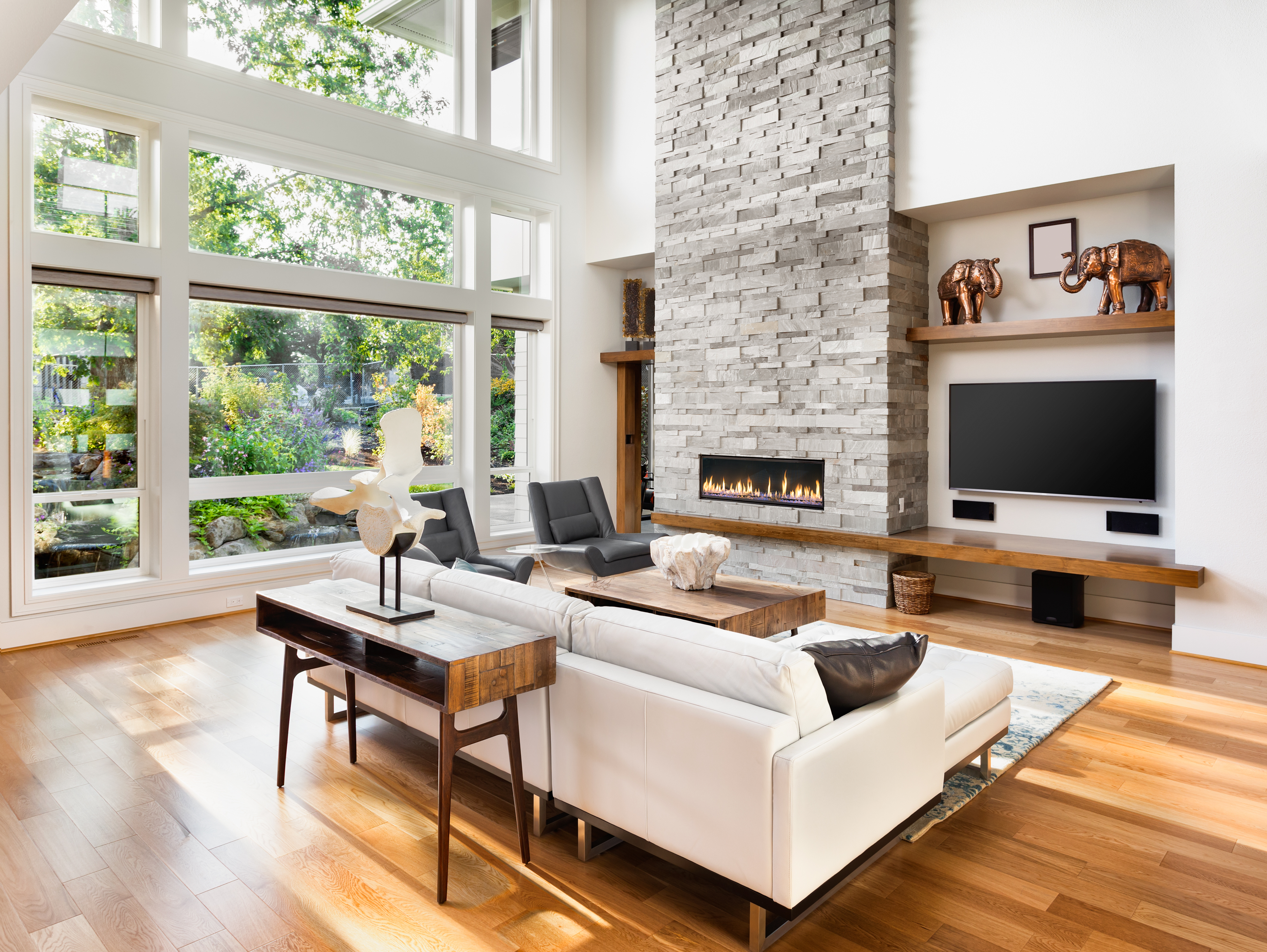 Beautiful living room interior with hardwood floors and roaring fire in fireplace in new luxury home