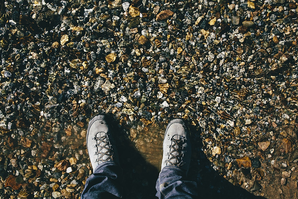 wet hiking shoes on gravel and shingle at a beach seaside