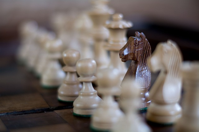 A black knight chess piece among white chess pieces