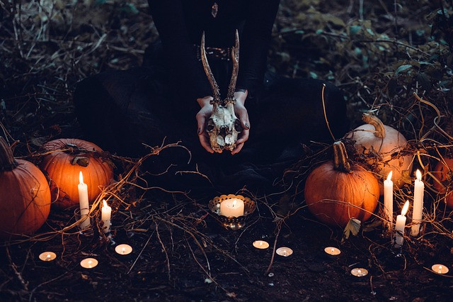 witch holding deer skull surrounded by candles and halloween pumpkins