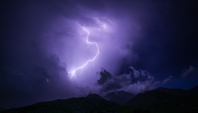 A lightning strike thunderbolt lights up a cloudy sky