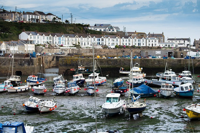 a cornish harbour full of boats at low tide in cornwall