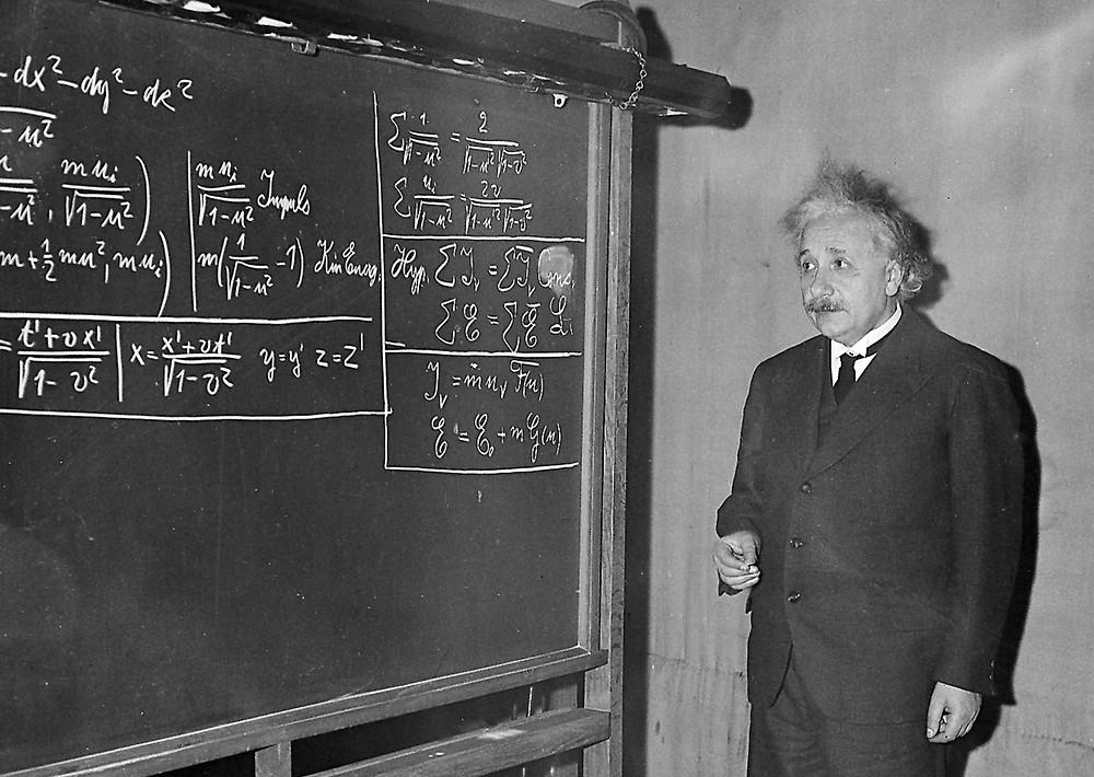 albert einstein writing algebra on a chalkboard