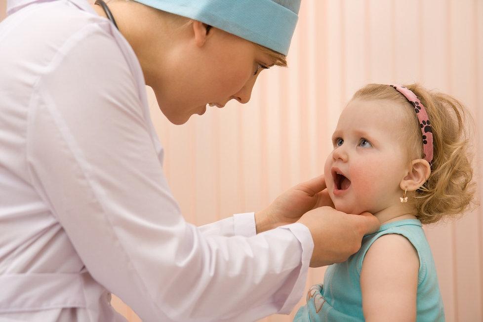 medica-examinando-a-boca-da-crianca-foto