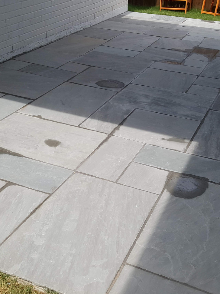 Thin cut patio stone laid in Ashlar pattern with a dark grey grout to match. Excuse the water, patio was still drying from post project washing!