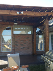 Freestanding pergola with custom wood patterned stamped concrete slab.
