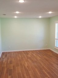This room was completely remodeled.  Drywall cracks/holes repaired, new texture, paint, lighting, trim and wood look tile that matched the original in the hallway.