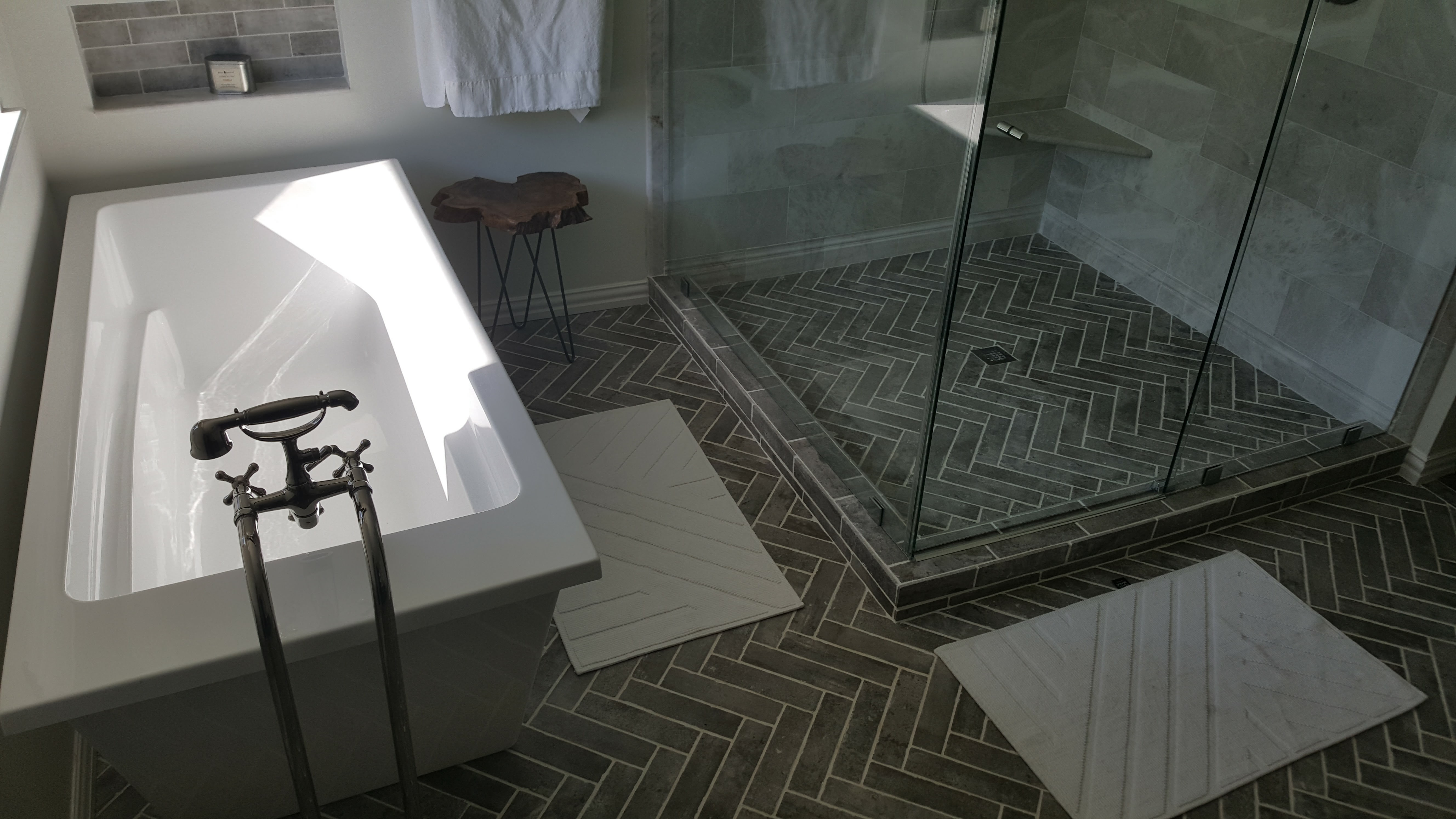 Bathroom remodel with herringbone brick floors, marble tiles and custom glass