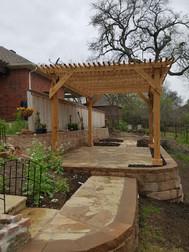 Segmental retaining wall backfilled with fresh top soil, new flagstone patios/walkways and pergola.