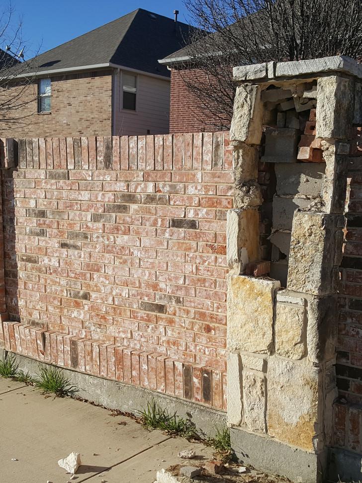 Stone column and brick fence damaged from vehicle impact.