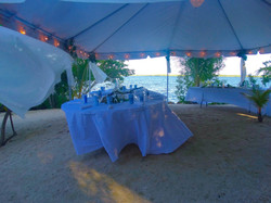 Dining by the water under a tent