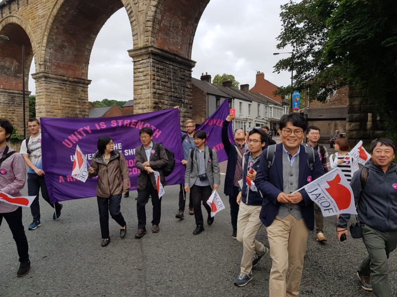 A group of people carrying flags and banners walking past a railway bridge