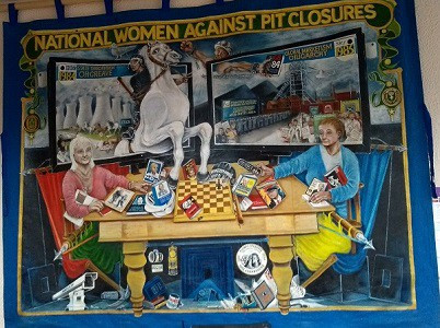 Banner with two women at a table and a range of images associated with mining and the 1984/5 strike
