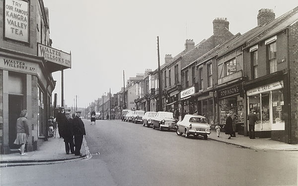Black and white image of Seaside lane high street. There are car parked one one side and people walking on the pavement and crossing the road