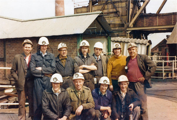 11 white men wearing hard hats and lamps, most in overalls, pose for  photo, colliery buildings are in the background