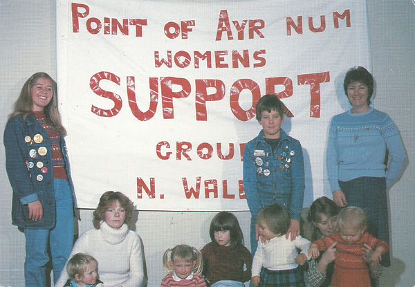 Five white women (two sitting and two standing) with five white children.  Two of the women are wearing lots of badges on denim jackets, the otehrs are in sweaters, They are in front of a banners that says  'Point of Ayr NUM Womens Support group N. Wales' in red letters on a white background
