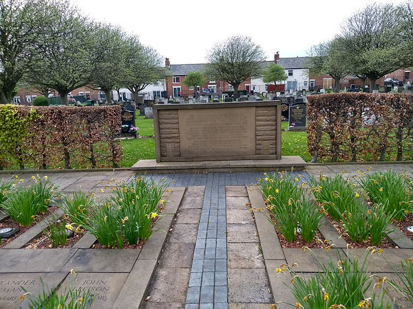 Colour photograph of memorial.  The foreground is daffodils planted next to stones with victims names. A memorial stone is in the mid-ground.