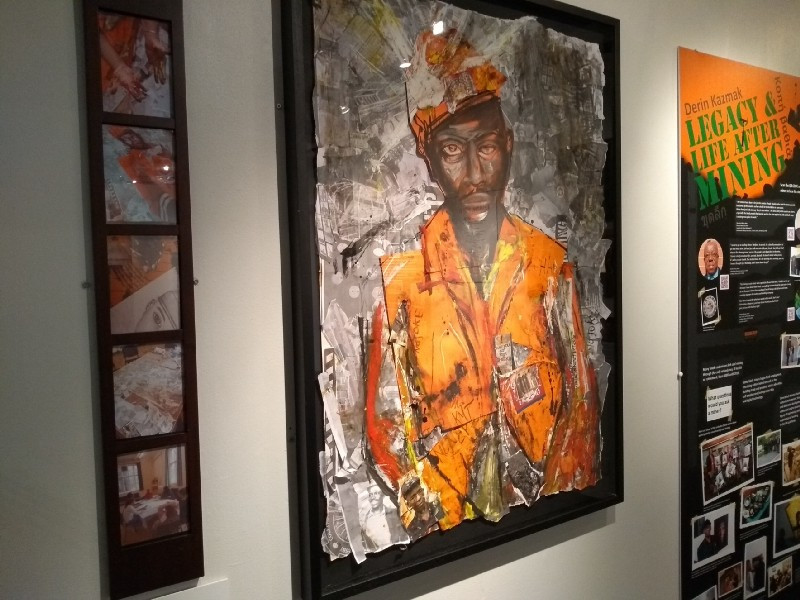 A museum display the centre of which is art depicting a black miner