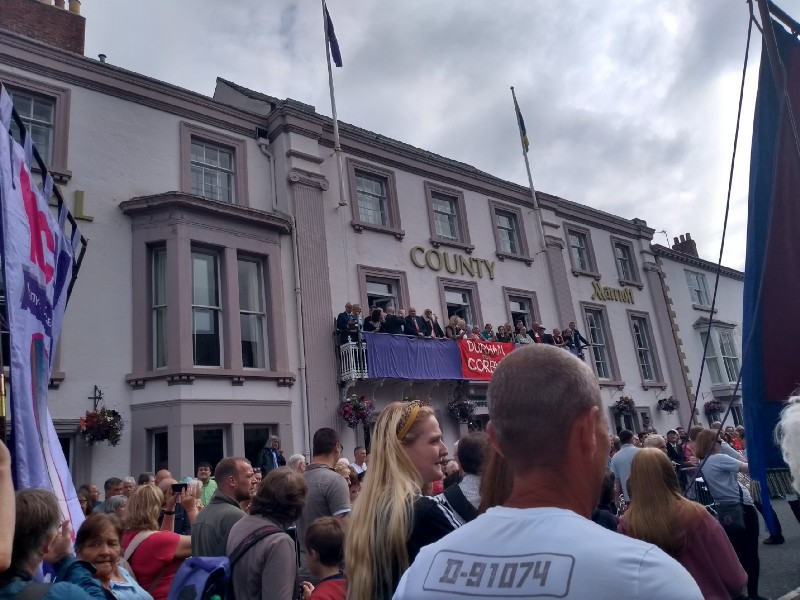 County Marriott hotel with people on the balcony and more people marching past.