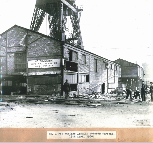 Black and white image of Markham. The image came with a caption 'No. 1 Pit Surface looking towards Screens, 19th April 1956.'.  There are five men in the foreground.  One of the buildings has a sign 'NO SMOKING HAVE YOU SEARCHED YOUR POCKETS'.  The bottom of the winding tower is also visible.