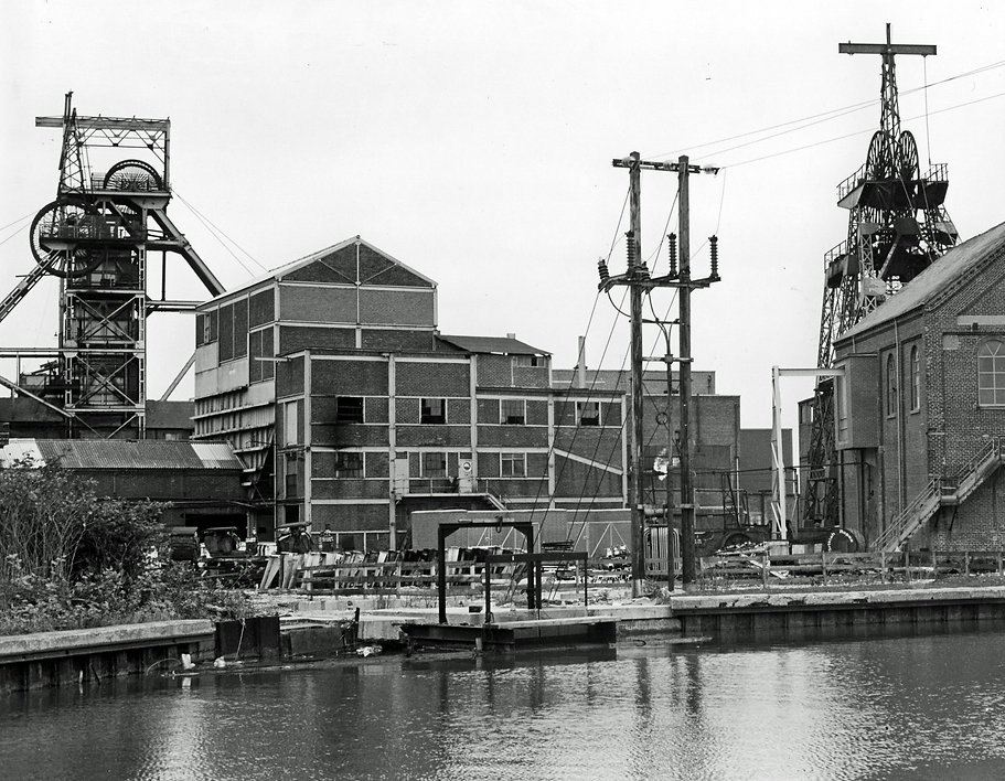 A black and white image of Bickershaw. A canal is in the foreground, the winding gear is on the left and right and other colliery buildings in between.