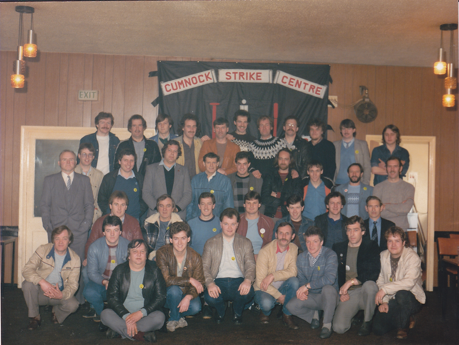 37 white men of a range of ages posing for a photograph in a hall.  Most are wearing yellow badges.  They are standing in front of a banner that says 'Cumnock Strike Centre'