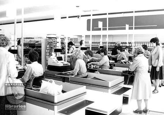A blakc and white image of the supermarket check out area, There are four checkouts in the foreground, and a number of women shopping at them.  The rest of the store can be seen in the background. There is a watermark saying 'Wakefield libraries'