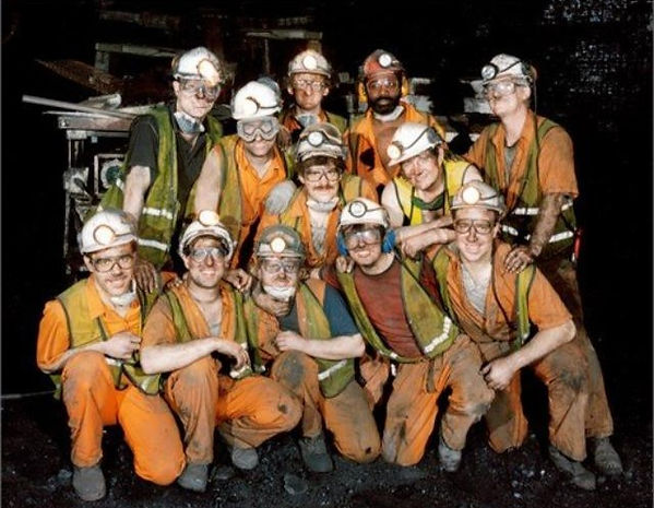 12 men, 11 white and one black wearing hard hats with lamps, vests with silver felectors, and orange overalls, posing for a photograph underground in a coal mine. There is some equipment in the background.