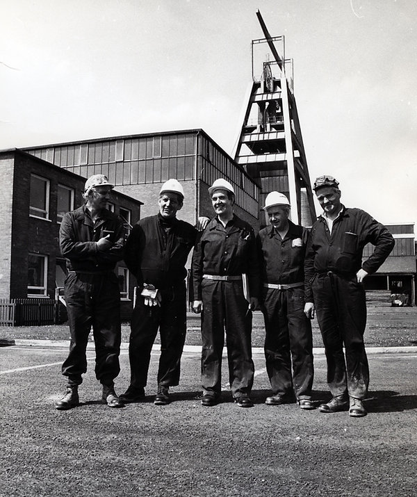 Black and white image five middle aged white men in the foreground. The Barony a frame and colliery buildings in the background.