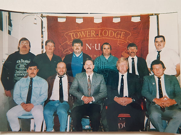 Eleven white men posing for a photograph in front of the Tower lodge banner.  Some are wearing suits and ties, some are dressed more informally.