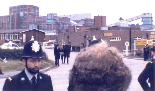 Colour picture of the police arresting someone. The background is Bentinck colliery and the foreground is three policemen and the back of a picket's head