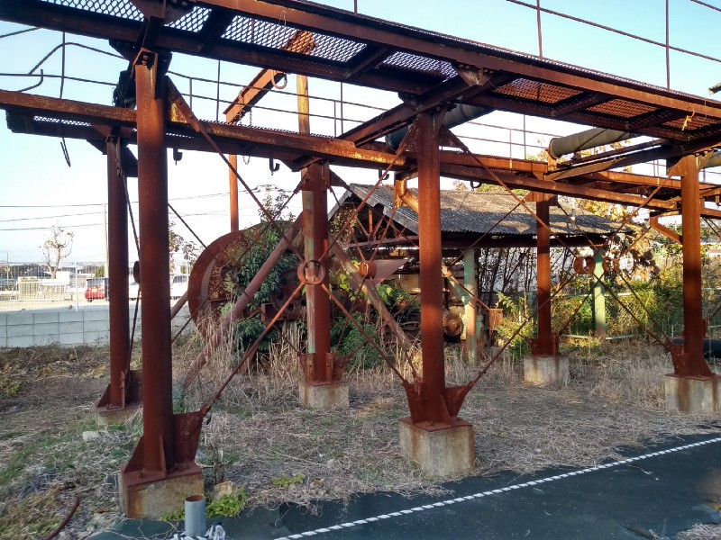 Rusty mine machinery with greery growing around it