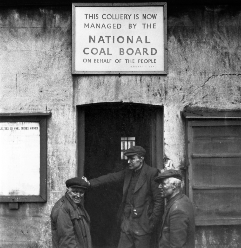 Image of three men with coal on their faces underneath a sign that says 'This Colliery is Now Managed by the National Coal Board On Behalf of the People'