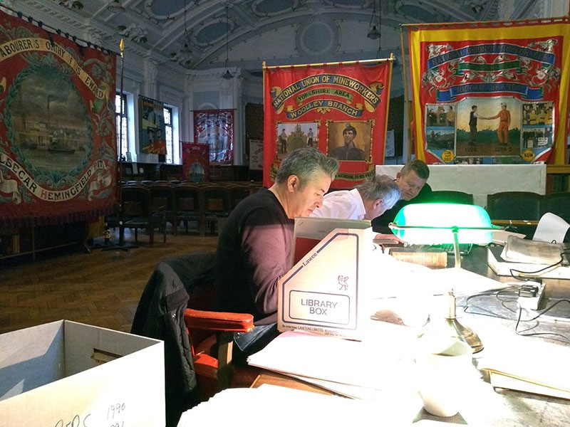 Three researchers working at a table in the foreground with banners in the background