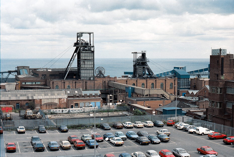 Colour image of Easington colliery with car park in the foreground and the North sea in teh background
