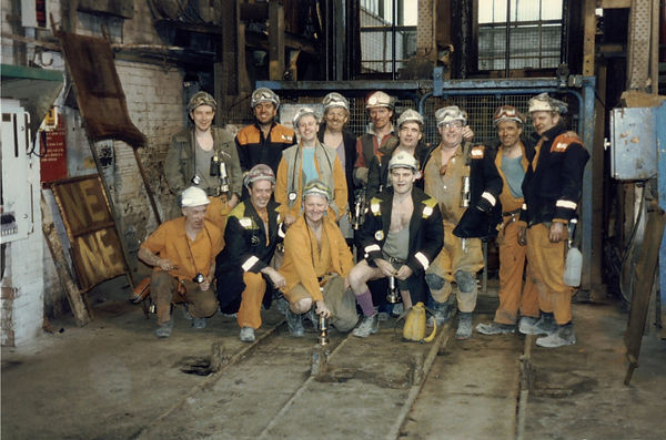 13 men wearing helps and orange overalls, posed for a photograph in an industrial setting