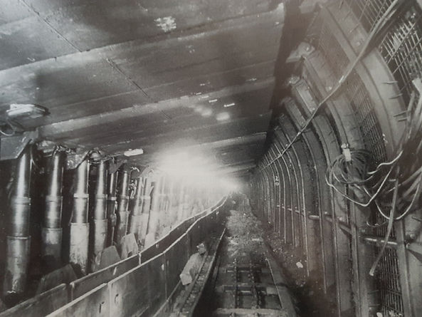 Black and white image of a coalface underground at Tower Colliery. The main focus of the image is the large and high-powered machinery installed at the coalface, especially the hydraulic chock supports and illuminated steel roof canopies.