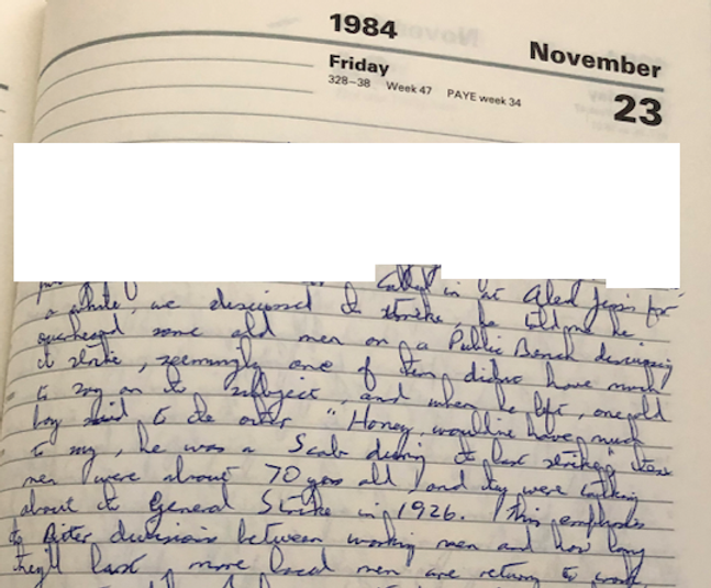 An image from a diary (dated 23 November 1984).  Some material has been blanked off in white.  Material is handwritten in blue pen.
