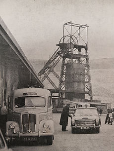 A black and white image with two vehicles in the foreground.  One vehicle is behind the other and there is a person next to the vehicle.  Tower Colliery is in the background
