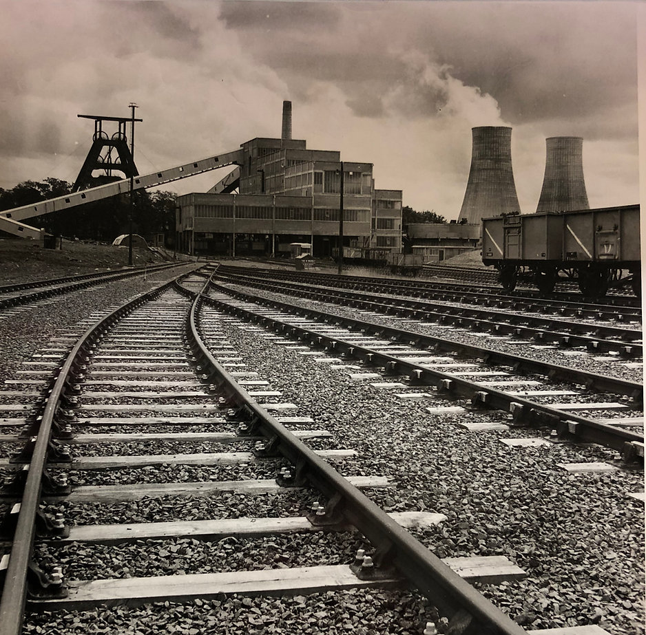 Image of Barony.  Railway tracks are in the foreground.  The A-frame is on the left, colliery buildings in the middle, and cooling towers on the right.