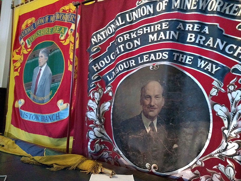 A banner depicting Dennis Skinner next to a banner depicting Clement Attlee