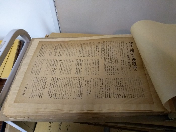 A large pamphlet coverd in Japanese text.  The pamphlet is stuck to a volume that is bound on the left.