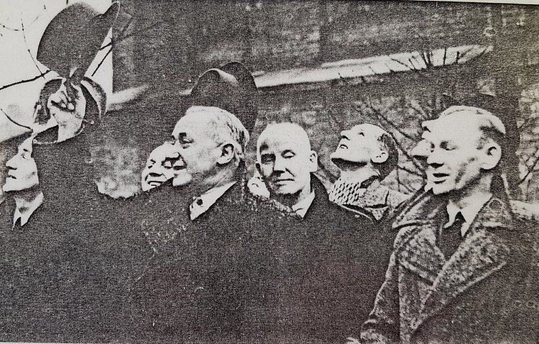 Black and white photograph of a group of men. Shinwell is in the centre raising his hat