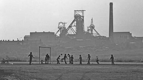 Black and white image of children playing football, with Bikershaw in the background