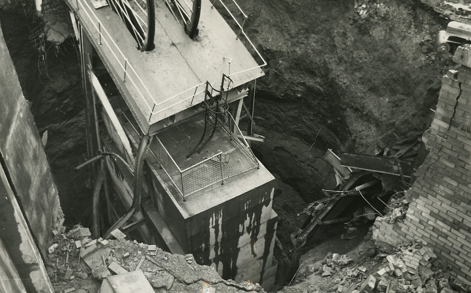 Black and white image of shaft collapse. The broken shaft is centre of the image, with other damaged materials in the foreground