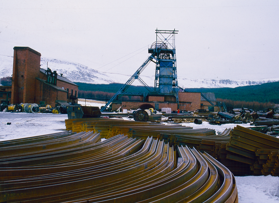 Colour image of Tower colliery in the snow.  There are girders in the foreground and the winding tower and other colliery buildings in the background.